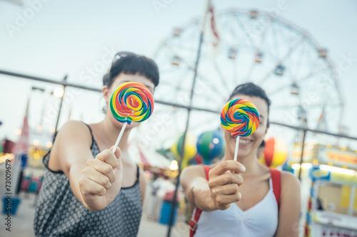 Poster Amusementspark Happy Young Women eating Lollipop