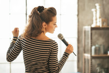 Young Woman Singing With Microphone. Rear View