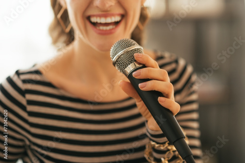 Fototapeta Closeup on young woman singing with microphone in loft apartment