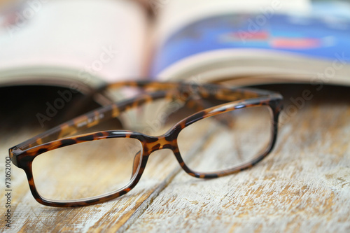 Fotomural  Reading glasses and open book on rustic wooden surface