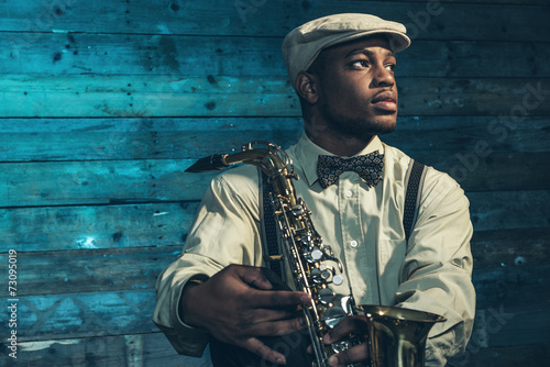 African american jazz musician with saxophone in front of old wo Canvas Print