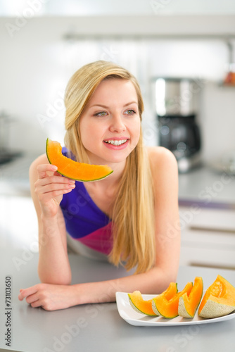 Happy Young Woman Eating Melon In Kitchen Buy This Stock
