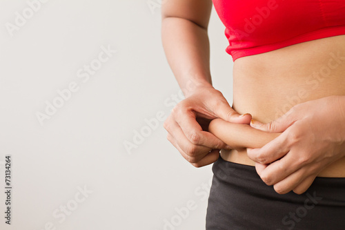 Fototapeta Woman's hand pinching her excess belly fat obraz