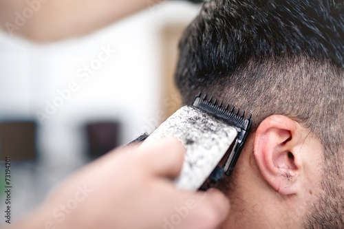 Fotomural men's hairstyling and haircutting with hair clipper in a barber