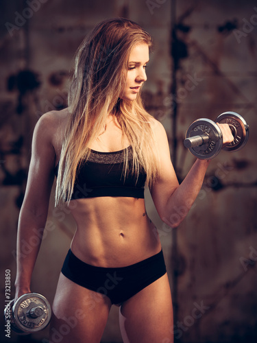 Photo  attractive young woman working out with dumbbells in an abandone