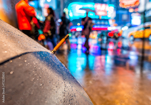 Photo  Open umbrella on a rainy night in Times Square - New York City