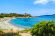 Beach with azure sea and castle on coast of Sardinia island