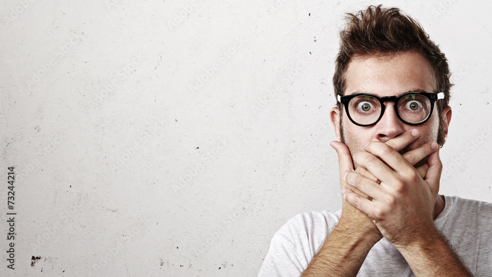 Fototapeta Shocked man covering his mouth with hands