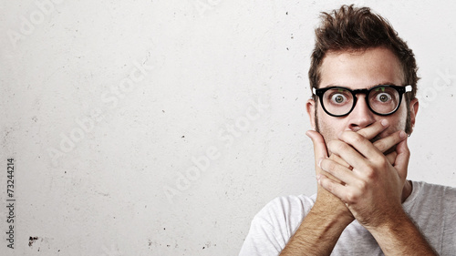 Fotografija  Shocked man covering his mouth with hands