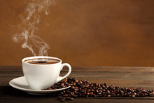 Black Coffee In White Cup With Smoke And Coffee Beans On Brown B