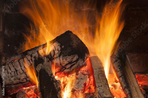 fototapeta na lodówkę Przytulny płonący ogień w kominku