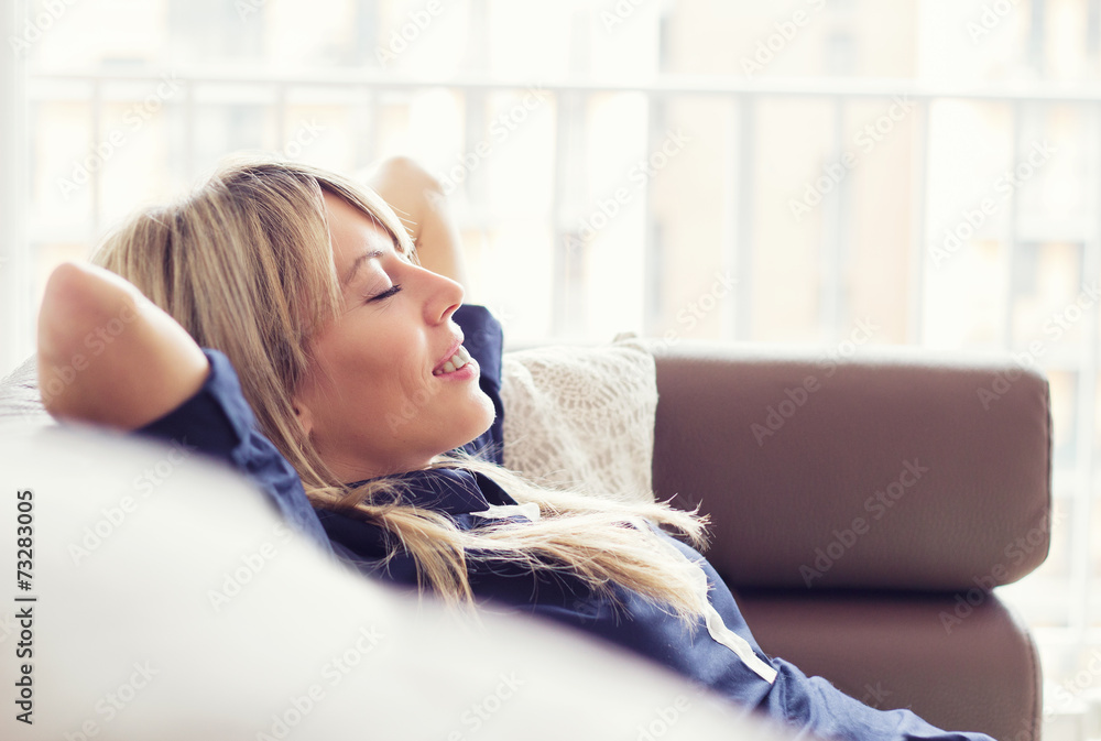 Fototapeta Relaxed young woman lying on couch