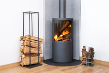Modern Burning Stove Next To A Wood Logs Rack