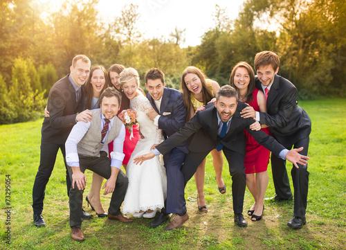 Slika na platnu Newlyweds with guest posing in park