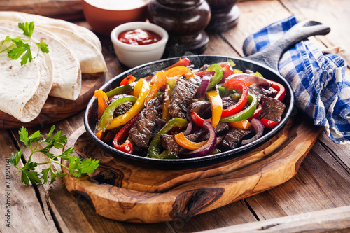 Fényképezés  Beef Fajitas with colorful bell peppers in pan and tortilla brea