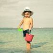 little boy playing on the beach at the day time