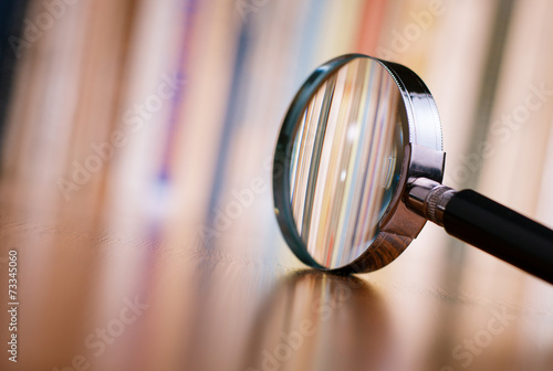 Valokuvatapetti Close up Magnifying Glass Leaning on Wooden Table