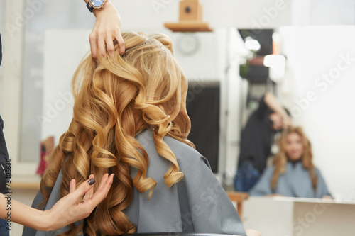 Tuinposter Kapsalon Blonde curly hair. Hairdresser doing hairstyle for young woman i