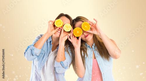 Dziewczyna bawić się z owoc nad żółtym tłem