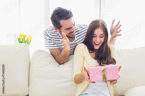 Man surprising his girlfriend with a gift on the couch Fototapet