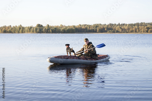 Deurstickers Jacht The hunter and hunting dog float on the lake after duck hunting