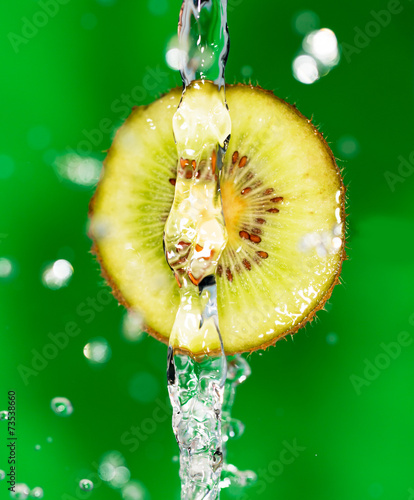 kiwi fruit in a spray of water on a green background