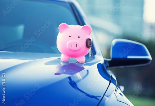 Fototapeta new car with piggy bank, key on hood obraz