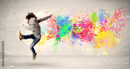 Poster Graffiti Happy teenager jumping with colorful ink splatter on urban backg