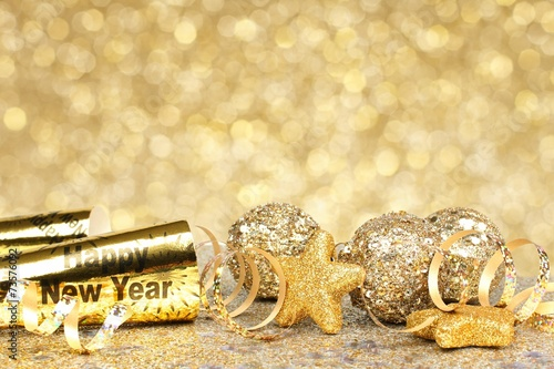 New Years Eve confetti and golden decorations on twinkling gold Poster