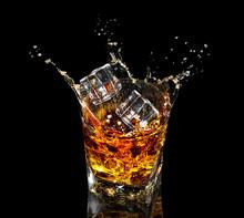 Glass Of Whiskey With Splash On Black Background