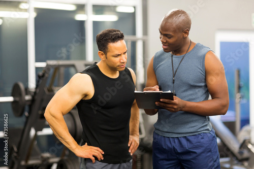 Fotografía  african personal trainer helping man to fill the membership form
