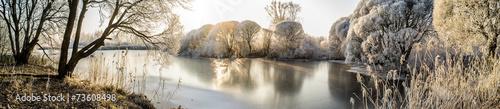 fototapeta na szkło Panorama zamarzniętego jeziora i ośnieżone drzewa