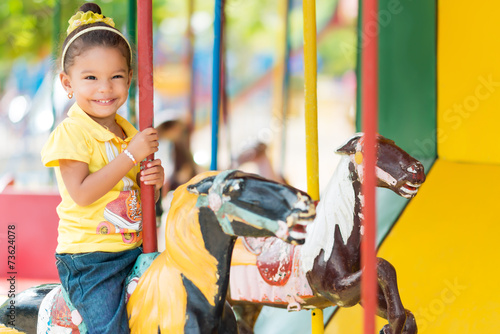 Foto auf Leinwand Vergnugungspark Cute mixed race girl riding a carousel