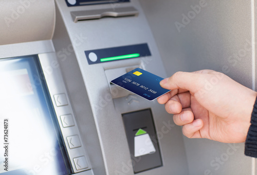 Fototapeta man puts credit card into ATM