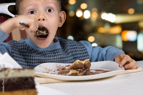 Fényképezés  Hungry little boy gobbling down a slice of cake