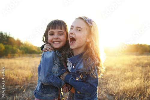 Fotografie, Obraz  Two cheerful friends snuggling outdoors in the park