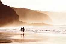 Couple Walking On Beach With Fog