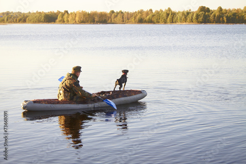 Foto op Canvas Jacht The hunter with an okhotnchy dog floats by the boat