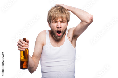 Fotografie, Obraz  Young man with hangover holding beer bottle
