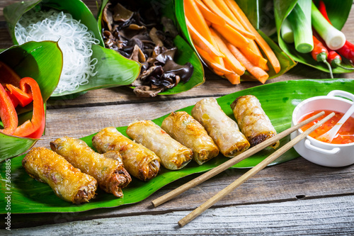 Fototapeta Fried spring rolls surrounded by ingredients obraz