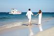 Loving couple walking on sandy beach.