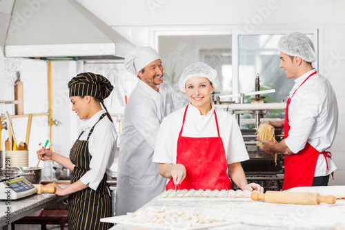 Photo  Confident Chef Cutting Ravioli Pasta With Colleagues In Backgrou