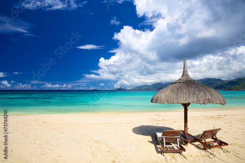 Perfect tropical beach with chairs and umbrella Canvas Print