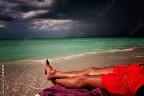 Photo Lonely men lying on the beach in Cuba