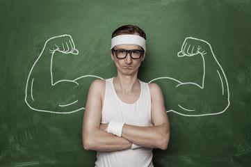 Fototapeta na wymiar Funny sport nerd with fake muscle drawn on the chalkboard