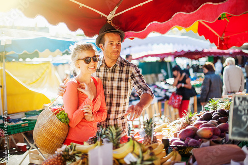 Photo  a young couple buying fruits and vegetables at a market