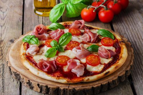 pizza with mozzarella and prosciutto, tomatoes
