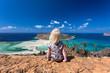 Cute girl sitting on a rock facing Balos beach on Crete, Greece