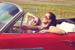 Beautiful ladies with sun glasses riding a vintage retro car