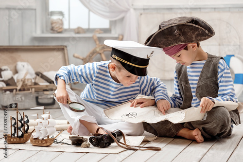 Valokuva  Boys dressed as a pirate captain and read travel map